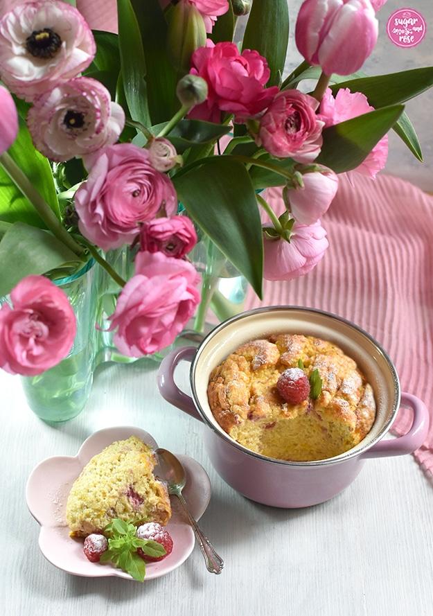 Hirse-Topfenauflauf mit Himbeeer-Garnitur im rosa Reindl, davor ein blütenförmiger rosa Teller mit einem Stück Auflauf, Himbeeren und einem silbernen Teelöffel, dahinter die Aalto-Vase mit rosa Tulpen und Ranunnkeln.