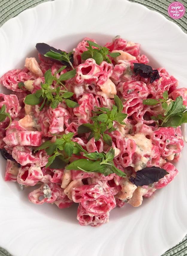 Rosa Pasta in Häschenform mit Lachs und Gorgonzolacreme, dekoriert mit grünem und rotem Basilikum
