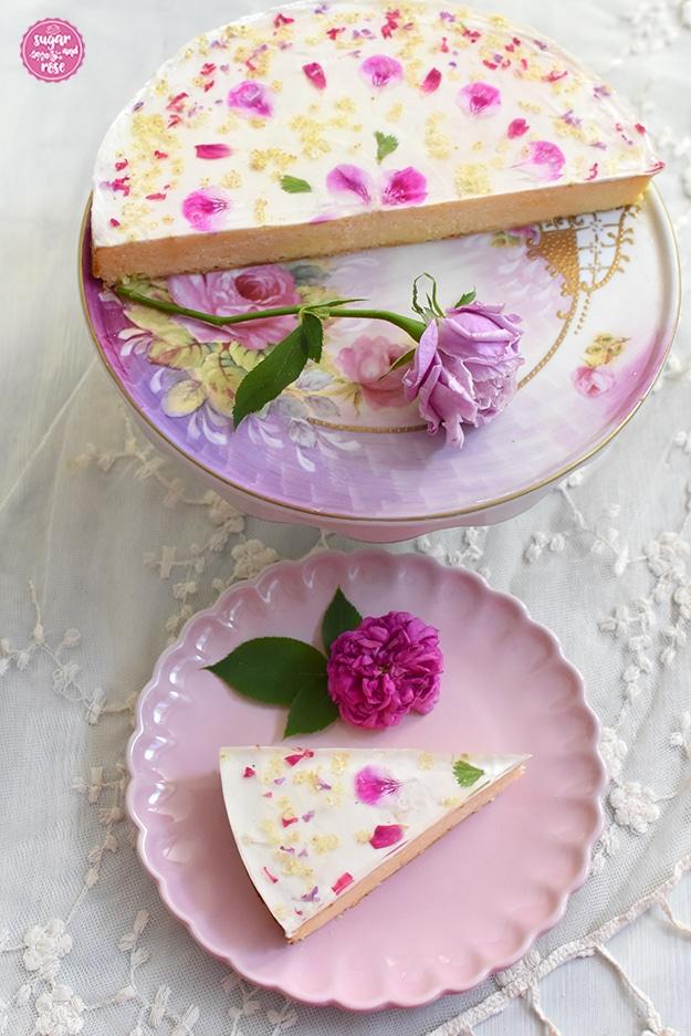 Zur Hälfte angeschnittene Topfentorte mit Blüten auf einer Porzellan-Etagere mit Rosendekor sowie eine lilafarbene Rose. Davor ein rosa Keramikteller mit einem Stück Topfentorte und einer pinkfarbenen Rosenblüte.
