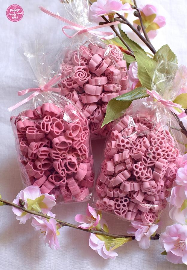 Drei Packungen hellrosa Blütennudeln in Häschen-, Blumen- und Rosenform in Cellophan mit rosa Schleife auf einem Kirschblütenzweig
