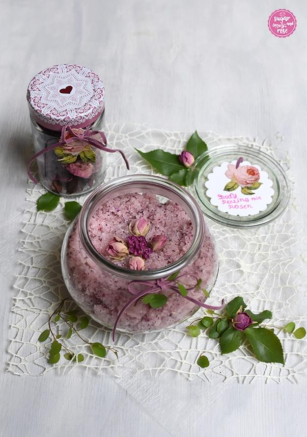 Ein großes bauchiges Rexglas gefüllt mit Rosen-Body-Peeling, dekoriert mit kleinen getrockneten rosa Rosenknospen, dahinter ein Glas mit getrockneten Rosenblüten und der Deckel des Glases mit Beschriftung in Rosa