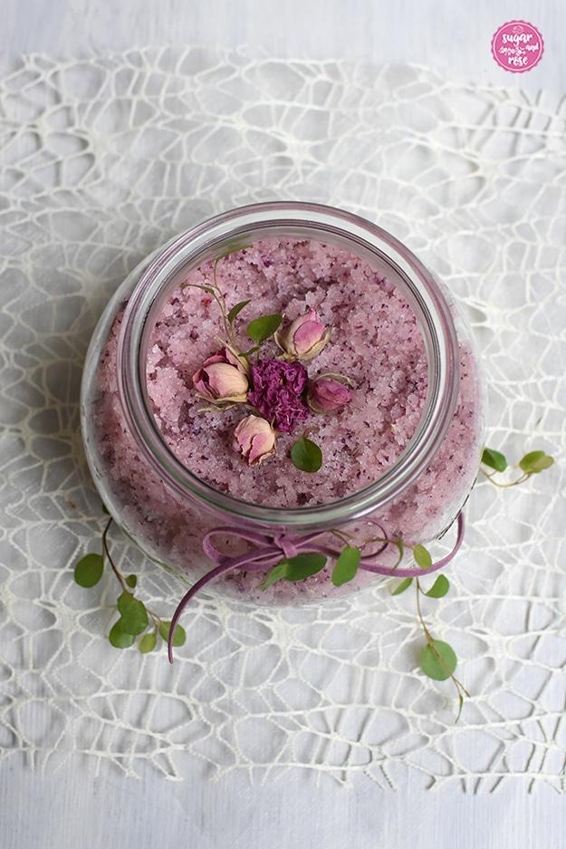 Offenes Rexglas von oben, man sieht das körnige rosa Peelingsalz, das Glas steht auf einem weißen netzförmigen Deckerl und ist mit grünen kleinen Blättern und eine rosa Masche dekoriert
