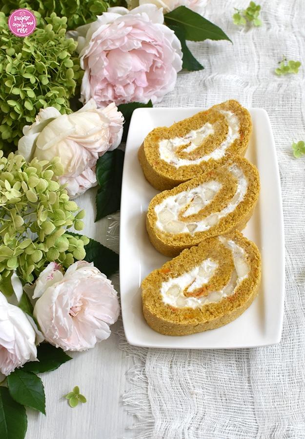Drei Stück Kürbisroulade gefüllt mit Birnen und Mandelcreme auf weißem rechteckigen Porzellanteller, daneben grüne Hortensienblüten und blassrosa Rosen