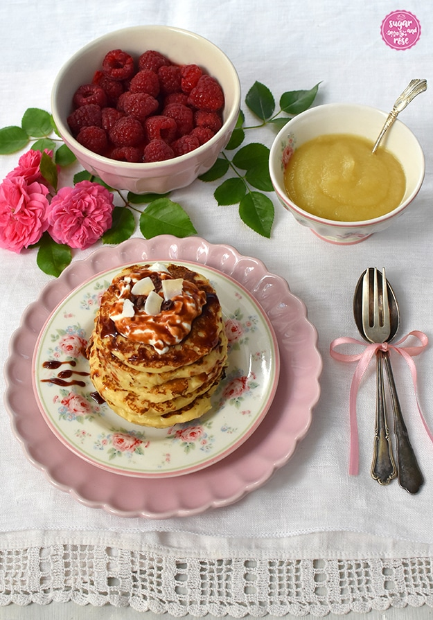 Pancakes auf Blütenteller und rosa Unterteller, daneben Silbergabel und Löffel mit rosa Schleife, dahinter eine Schale mit Himbeeren und eine mit Apfelmus, dekoriert mit rosa Rosen