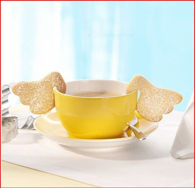 cookie cutter wings hanging cookie off of yellow mug