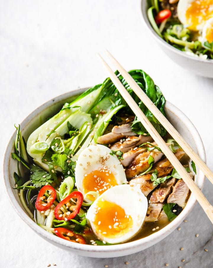 a bowl with keto ramen cntaining chicken, vegetables and a halved soft boiled egg and chopsticks