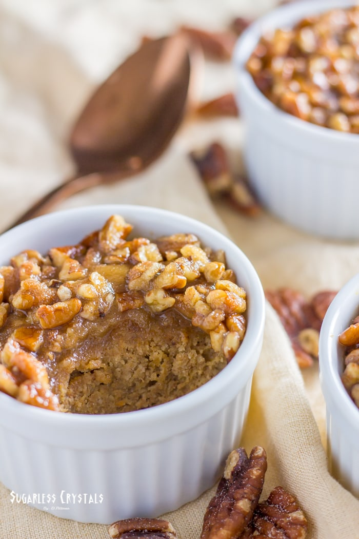 pecan pumpkin spice keto mug cake with spoonful taken out surrounded by pecans