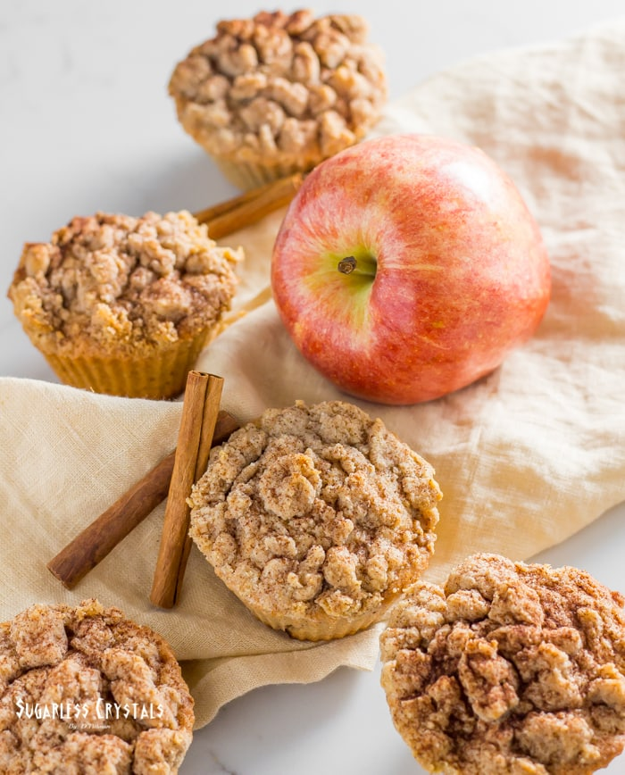 Healthy apple muffins laid out with apple and cinnamon sticks