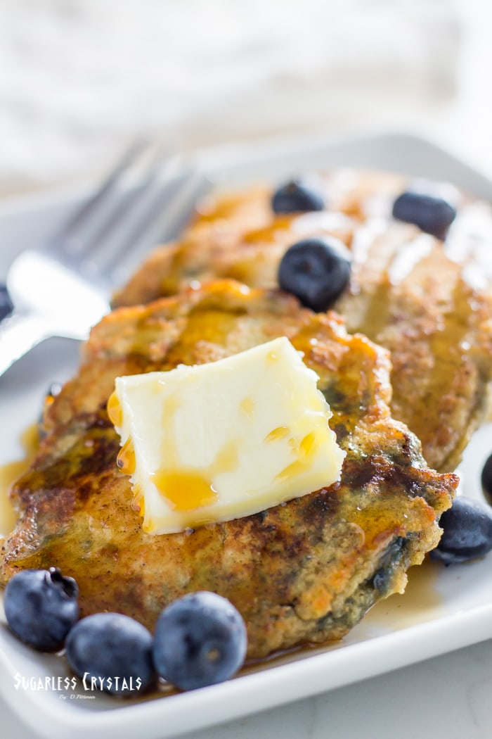 Keto pancakes with coconut flour with mixed in blueberries topped with butter and sugar free maple syrup