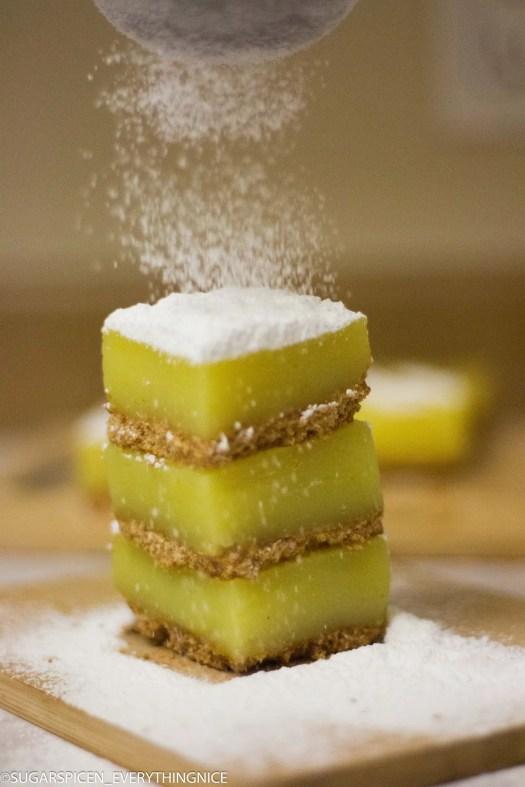 Three lemon bars with powdered sugar falling on top.
