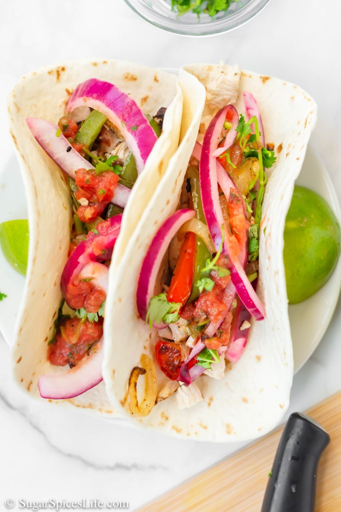 Chicken marinated in a cilantro, lime sauce, then grilled, placed in a tortilla, and topped with grilled vegetables and pickled red onions. These Grilled Cilantro Lime Chicken Tacos are taco perfection.