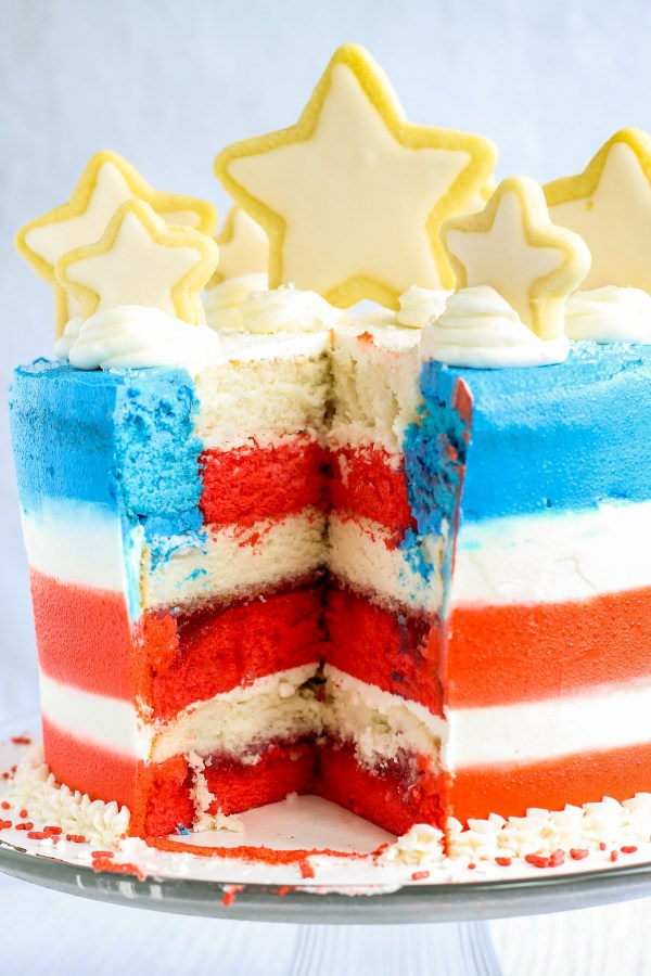 This flag cake is not only beautiful, but delicious! A white, almond cake with raspberry filling, and decorated with the best ever sugar cookies. It's perfect for the 4th of July, Memorial Day, or Labor Day!