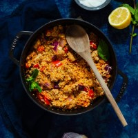 One Pot Harissa Chicken. Deliciously flavored harissa chicken mixed with sauted vegetables and couscous, topped with a yogurt mint sauce. All the cooking is done in one pot for easy prep and cleanup!