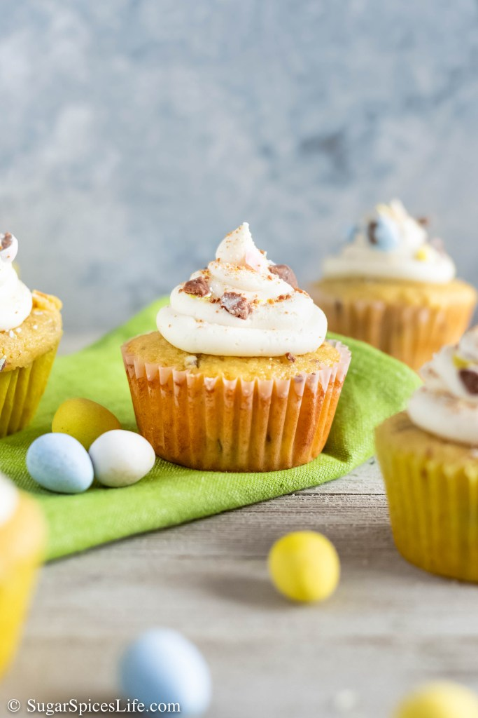 These Cadbury Mini Egg Cupcakes are soft vanilla cupcakes with bits of candy eggs, a chocolate ganache filling, vanilla buttercream frosting, and a Cadbury egg topping.
