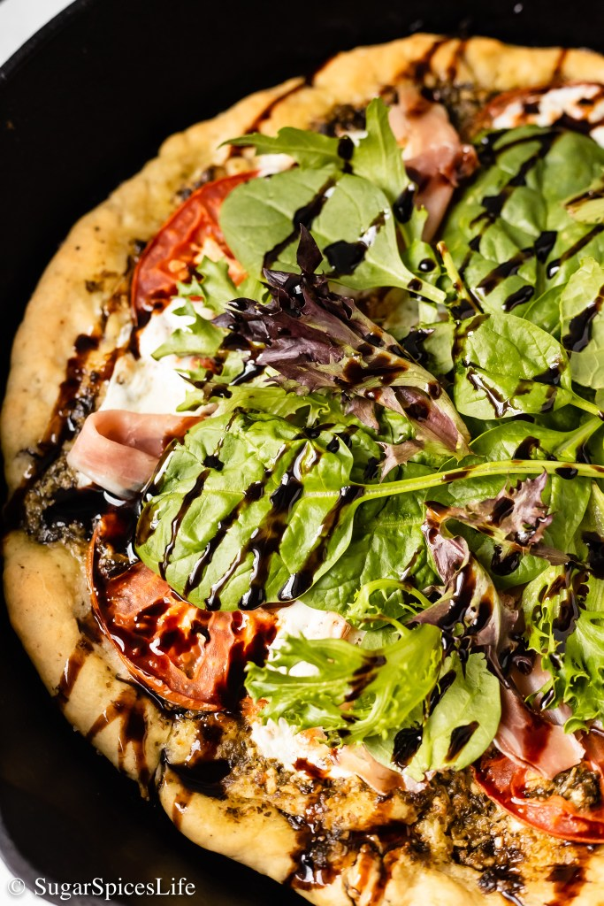 A soft, fluffy crust topped with pesto, fresh mozzarella, prosciutto, greens, and  balsamic reduction. This homemade Prosciutto Caprese Skillet Pizza is just as tasty as takeout!