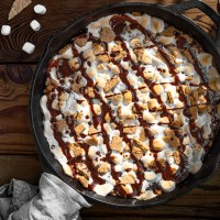 Rich, fudgy brownies with a graham cracker crust, topped with roasted marshmallows and chocolate syrup. This Skillet S'mores Brownie is an delicious, easy dessert for any time of the year!