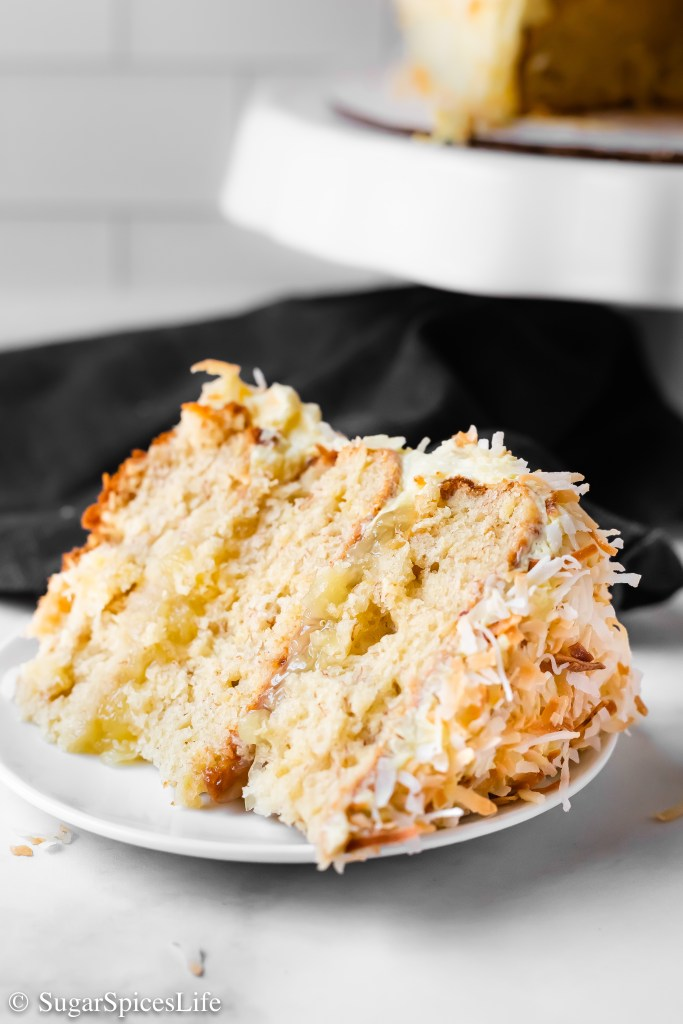 Fruity, soft cake layers filled with crushed pineapple, frosted with a vanilla coconut milk frosting, and covered with toasted coconut and dried pineapple decor. This Pineapple Coconut Cake is a beautiful, delicious dessert!