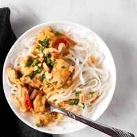 Chicken in a savory peanut butter sauce, served over rice noodles with peanuts, green onions, and cilantro. This Slow Cooker Peanut Chicken is the perfect meal to come home to after a busy day!