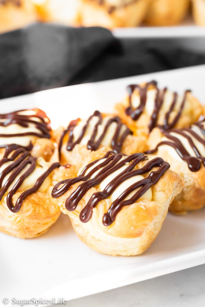 Vanilla cream in a puff pastry crust, finished with a chocolate glaze. These Chocolate Eclair Puffs are decadent, individually sized dessert treats!