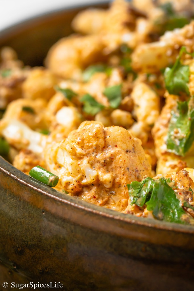 Cripsy, roasted cauliflower coated in a flavorful, creamy sauce, then tossed with crumbled Queso, green onions, and cilantro. This Mexican Street Style Cauliflower is an easy and delicious side or appetizer!
