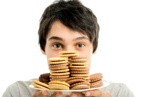 Man in love with sweets, candies,chocolate and sugar but trying to withhold. Forbidden sweets for a healthy longer life