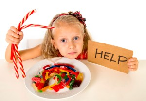 sad and vulnerable Caucasian female child asking for help eating dish full of candy and gummies holding sugar spoon in sweet abuse dangerous diet and unhealthy nutrition concept isolated on white
