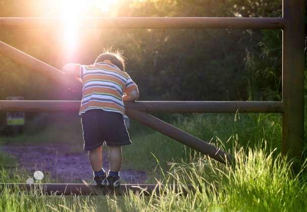 SugaShoc_Photography_Children_Photographer_Bucks County_Doylestown_PA_child_gate_hanging_onto_the_fence