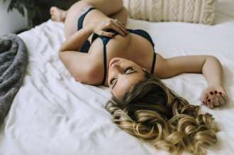 Sugashoc Photography Fiance Boudoir layingon bed wearing black bra and panty hand on breast
