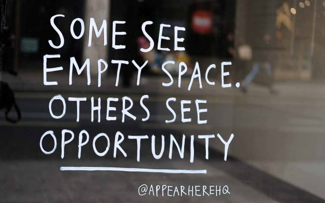 window sign that says 'Some see empty space. Others see opportunity'.