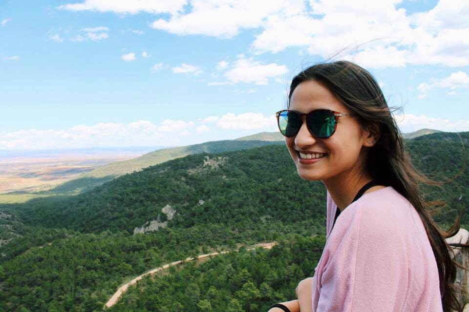 Maya wearing sunglasses on the hillside