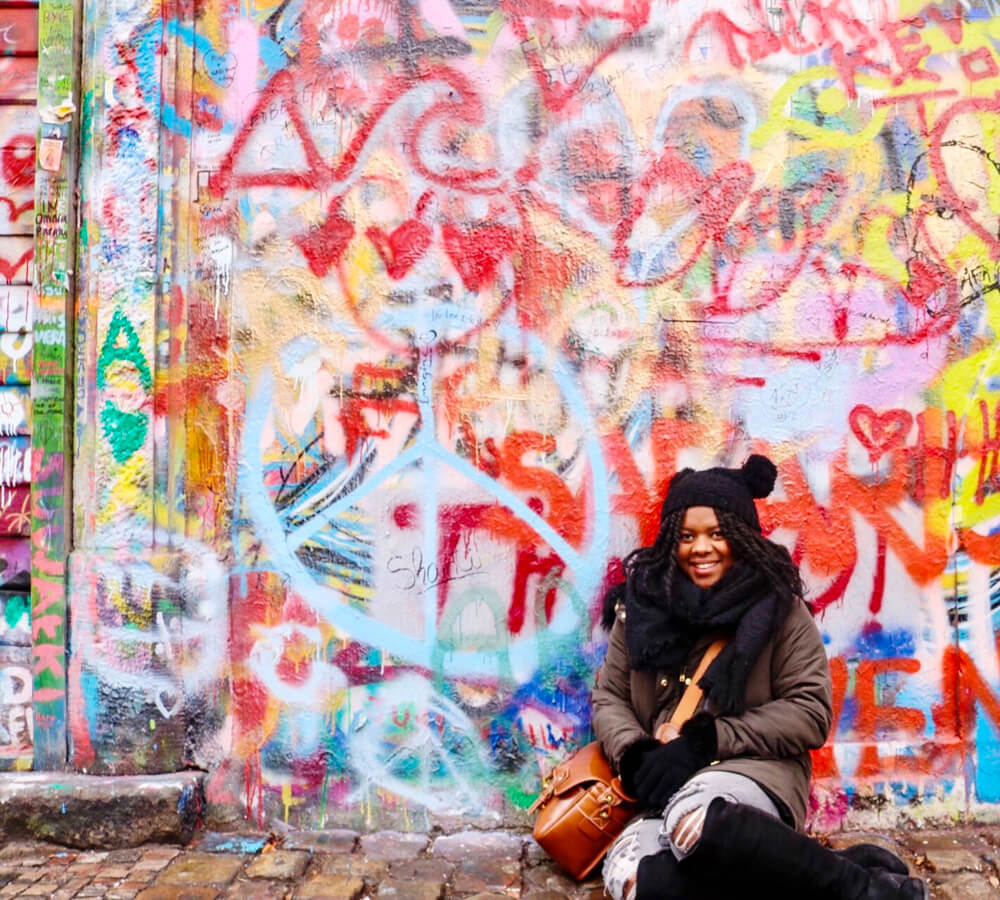 Sojourner posing in front of a graffiti wall