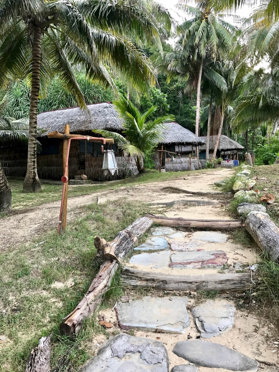 A stone path leads up to the rimba resort grounds with bamboo thatched roofs