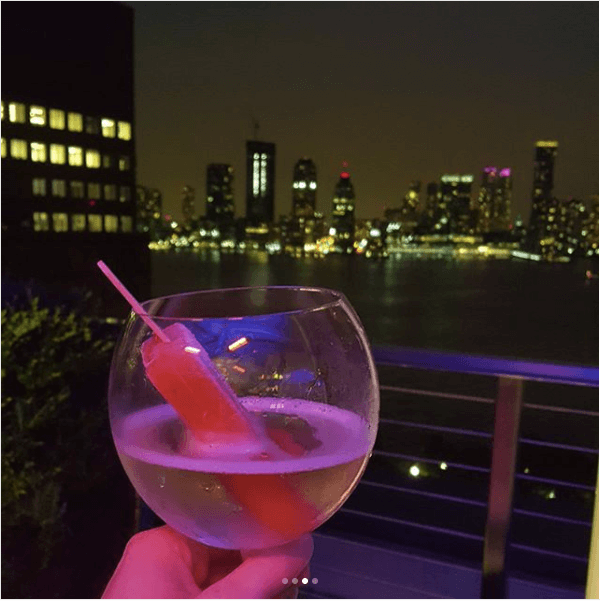 Picture of a cocktail with a popsicle in it over the NYC skyline