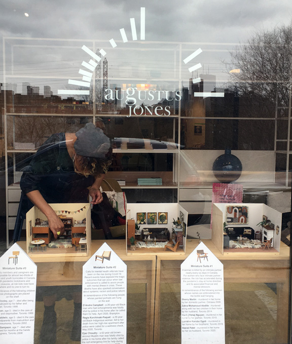 artist setting up miniature window installation