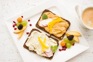 Zwei Vollkornbrötchen mit Auftstrich und Obst: Mit gesunder Ernährung erfolgreich abnehmen.