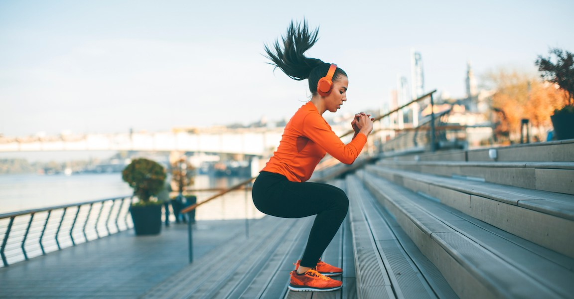 Sportliche Frau springt in die Kniebeuge.