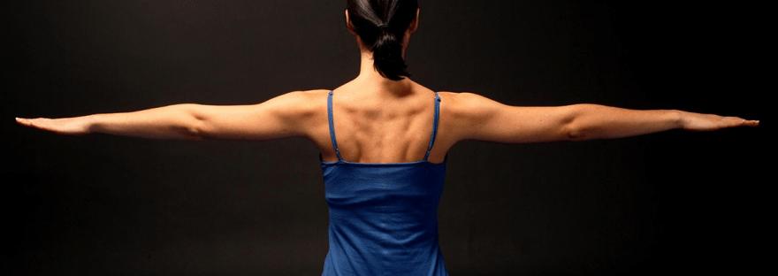 Pilates-Übungen: Man sieht den Rücken einer Frau. Sie streckt die Arme seitlich aus. Man sieht volle Körperspannung.