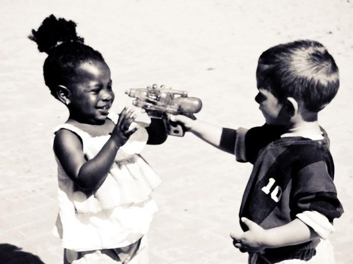 sw-Foto, kleine Kinder spielen Spielzeugpistole
