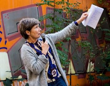 Foto: Frau am Mikrofon zeigt auf Schule