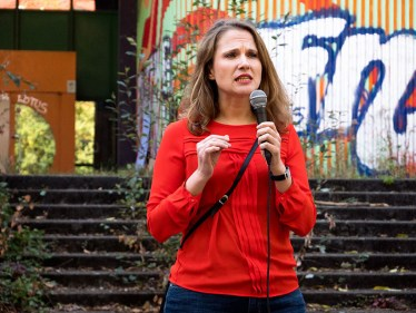 Foto: Frau am Mikrofon vor ehemaliger Schule