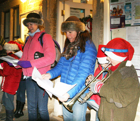 Carol singers tune up outside the community shop