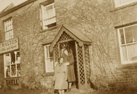 Cecil Walton's daughter Edith (later Edith Parker) on the top step of the cottage with wartime evacuee Renee Barrett c1942. Cecil ran a motor cycle parts and fuel supply business from the garage adjoining the property.