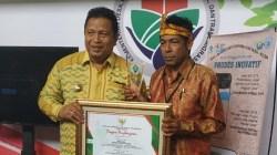 Kepala Desa Lakandito Jafarudin (kanan) foto bersama Bupati Muna Rusman Emba usai menerima piagam penghargaan dari Kemendes PDTT. Foto: IST