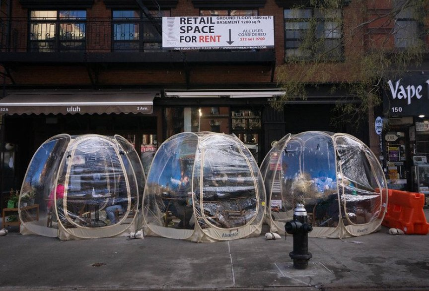 Plastic bubbles for outdoor dining line the sidewalk outside a NYC restaurant.