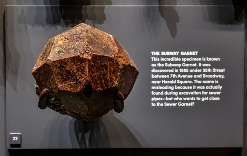 on a dark presentation backdrop, a rough looking stone with crude facts appears.