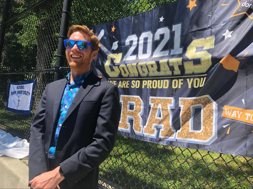 Kyle Brillante smiles while standing in front of a sign that says 2021 Congrats Grads
