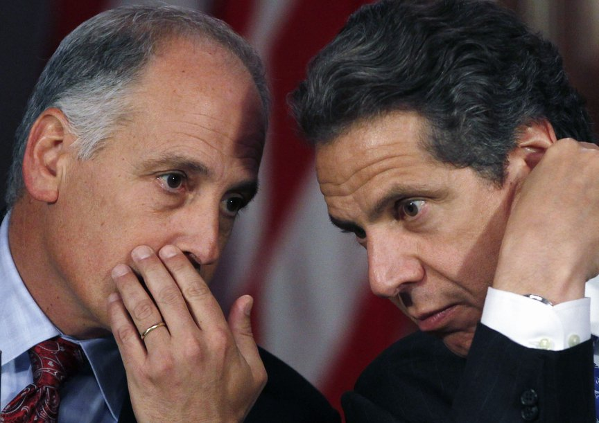 Close up of Larry Schwartz whispering, with his hand cupping his mouth, to Governor Cuomo who was leaning close