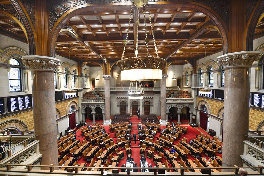 A view of the ornate NY State Assembly chamber, which has a soaring ceiling, a red carpet and pillars