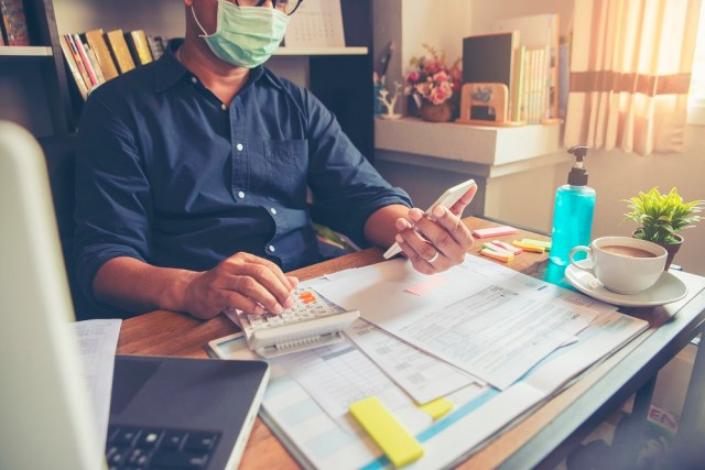 Budget planning concept, Accountant wear mask is calculating tax. Personal income tax forms placed on desk