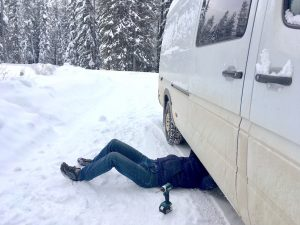 Lying under the van making repairs